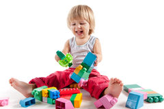Laughing little boy playing with colorful blocks. Isolated on white background Royalty Free Stock Photos