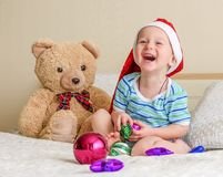 The laughing little boy in a red cap with toys. Stock Photo