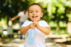 Laughing little boy running outdoor with a bottle of a clear drinking water, his father is blurred in the background. Importance. Little boy in a white shirt stock image