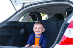 Laughing little boy sitting in the back of a car Royalty Free Stock Photo