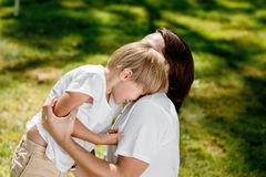 Laughing little boy in a white t shirt is playing with his handsome father in the open air in the park. stock photo