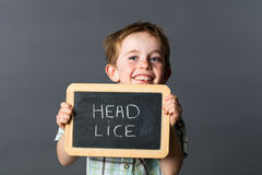 Laughing little child warning about head lice to fight against. Laughing little child with red hair warning about head lice to fight against at school with royalty free stock images