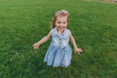 Laughing little cute child baby girl in denim dress walking and running, have fun on green grass lawn in park. Mother stock photos