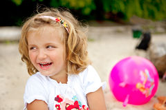 Laughing little girl. Young blond girl with blue eyes laughing and looking left stock photo