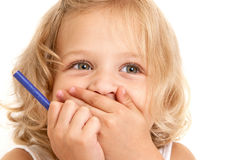 Laughing little girl. Covers her mouth with her hands and holding a pencil in her hand close-up on  white background Stock Photos