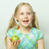 Laughing little girl with apple Royalty Free Stock Photos