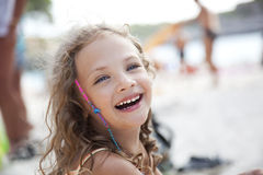 Laughing little girl on a beach Stock Photos