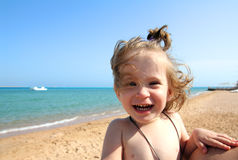 Laughing little girl on beach Stock Photos
