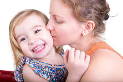 Laughing little girl being kissed by her mother Royalty Free Stock Images