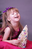 Laughing little girl with a Christmas tree Stock Image
