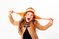 Laughing little girl in colorful sweater and hat isolated. Laughing little girl in colorful sweater and hat pulling her hat Stock Photo