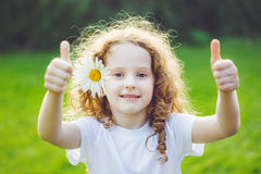 Laughing little girl with daisy in her hairs, showing thumbs up. Royalty Free Stock Images