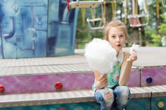 Laughing little girl eating candy floss at a fair Stock Photography