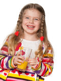 Laughing little girl with a glass of orange juice Royalty Free Stock Photos