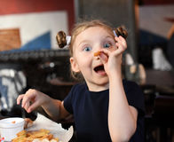 A laughing little girl having a dinner and paying with food royalty free stock photography