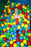 A laughing little girl having fun playing with multicolor plastic balls royalty free stock photos