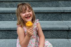 Laughing little girl holding an ice cream cone Royalty Free Stock Photo