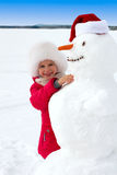 Laughing little girl hugging a snowman Royalty Free Stock Image