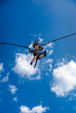 Laughing little girl jumping with rubber band and trampoline in the sky. Stock Photos