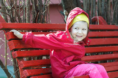 Laughing little girl leaning forward and sitting on red rest wood bench Stock Photography