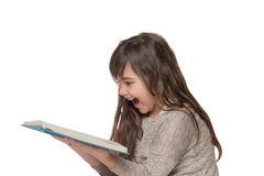 Laughing  little girl  leaning over an open book Royalty Free Stock Photos