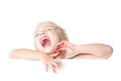 Laughing little girl looking over empty board Royalty Free Stock Photos