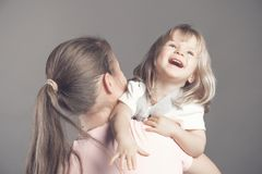 Laughing little girl looks happy in mother`s arms. Beautiful baby girl in the arms of a young mom. Woman holding her stock photos
