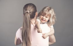 Laughing little girl looks happy in mother`s arms Beautiful baby girl pulls mom`s hair and smiling. Woman holding her stock photos