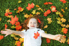 Laughing little girl lying in grass throws the autumn leaves in Royalty Free Stock Photography