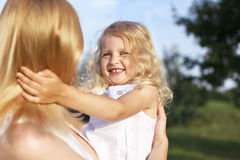 Laughing little girl in mother arms Royalty Free Stock Photo