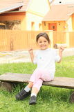 Laughing little girl. In pink trousers and t-shirt sitting on a bench Royalty Free Stock Images