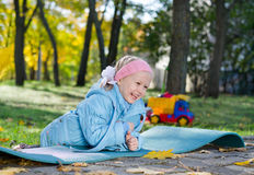 Laughing little girl playing in the park. Adorable laughing little girl playing in the park lying on her stomach on a mat Royalty Free Stock Photos