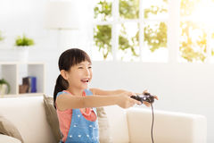 Laughing little girl playing video games on sofa Royalty Free Stock Photo