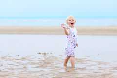 Laughing little girl plays on the beach Stock Photography