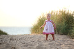 Laughing little girl plays on the beach Royalty Free Stock Image