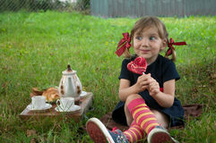 A laughing little girl presenting Pippi Longstocking, sitting on a garden grass and eating a lollipop Stock Image