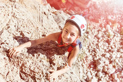 Laughing Little Girl in Protective Helmet climbing Rock Royalty Free Stock Photography