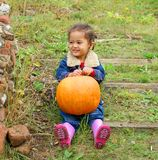 Laughing little girl and pumpkin Royalty Free Stock Photos