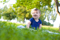 Laughing little girl sitting on the grass in summer Royalty Free Stock Image