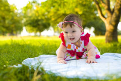 Laughing little girl sitting on the grass Stock Photography