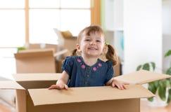 Laughing little girl sitting inside cardboard boxe in her new home. Laughing little girl sitting in cardboard boxe in her new home royalty free stock image