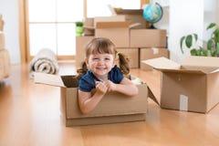 Laughing little girl sitting inside cardboard boxe in her new home. Laughing little girl sitting in cardboard boxe in her new home stock images