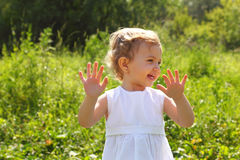 Laughing little girl standing in the grass Royalty Free Stock Images