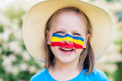 Laughing little girl in straw hat with painted face having fun. Royalty Free Stock Photos