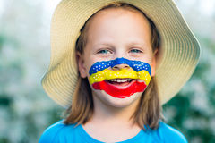 Laughing little girl in straw hat with painted face having fun Royalty Free Stock Image
