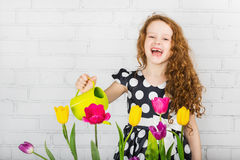 Laughing little girl watering tulips flower from can. Royalty Free Stock Photography