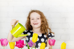 Laughing little girl watering tulips flower Royalty Free Stock Image