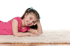 Laughing little girl on the white carpet. A laughing little girl is lying on the white carpet stock image