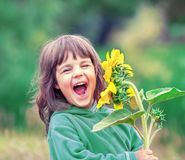 Free Laughing Little Girl With Sunflower Stock Image - 128282801