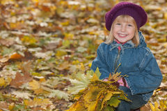 Laughing little girl with yellow leaves Royalty Free Stock Images